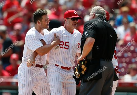 Cincinnati Reds manager David Bell (25) holds back Nick Senzel, left, just after Senzel was ejected from the game by home plate umpire Bill Miller, right, arguing a third strike call during the fourth inning of a baseball game against the Colorado Rockies, in Cincinnati