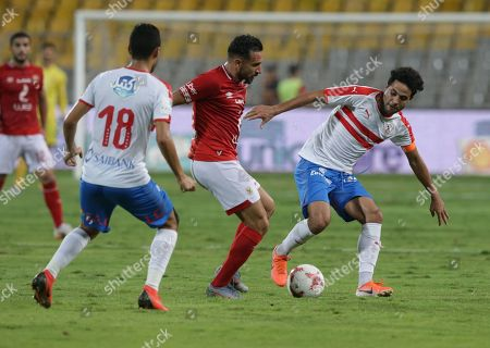 Zamalek players Mo Ibrahim (R) and Ibrahim Hassan (L) in action against Ahly player Ali Maaloul during the Egyptian league soccer match between Zamalek and Al-Ahly at Borg Al-Arab Stadium in Alexandria, Egypt, 28 July 2019.