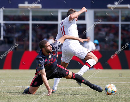 Benfica's Adel Taarabt and AC Milan's Fabio Borini vie for the ball during the first half of an International Champions Cup soccer match, in Foxborough, Mass