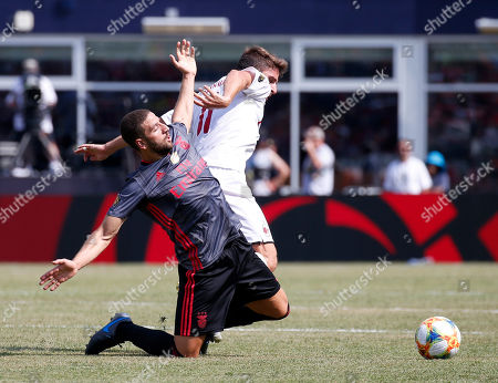 Benfica's Adel Taarabt falls to the turf battling for the ball against AC Milan's Fabio Borini during the first half of an International Champions Cup soccer match, in Foxborough, Mass