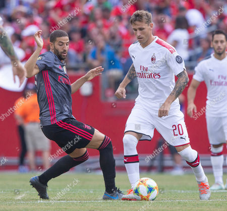 Benfica midfielder Adel Taarabt (L) fights for the ball with AC Milan midfielder Lucas Biglia (R) during the first half of their International Champions Cup match held at Gillette Stadium in Foxboro, Massachusetts, USA 28 July 2019.