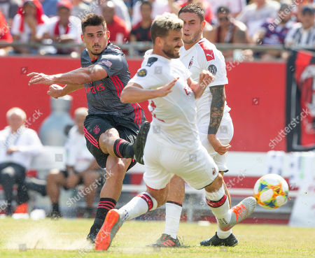 Benfica midfielder Gabriel (L) shoots past defending AC Milan defender Mateo Musacchio (C) and AC Milan defender Davide Calabria (R) during the first half of their International Champions Cup match held at Gillette Stadium in Foxboro, Massachusetts, USA 28 July 2019.