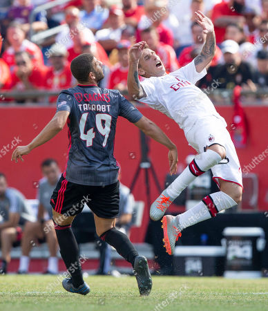 AC Milan midfielder Lucas Biglia (R) goes collides with Benfica midfielder Adel Taarabt (L) during the second half of Benfica's 1-0 win over AC Milan in their International Champions Cup match held at Gillette Stadium in Foxboro, Massachusetts, USA 28 July 2019.