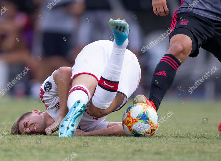 AC Milan midfielder Lucas Biglia crashes to the pitch during the second half of Benfica's 1-0 win over AC Milan in their International Champions Cup match held at Gillette Stadium in Foxboro, Massachusetts, USA 28 July 2019.