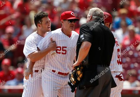 David Bell, Nick Senzel, Bill Miller. Cincinnati Reds manager David Bell (25) holds back Nick Senzel, left, just after Senzel was ejected from the game by home plate umpire Bill Miller, right, arguing a third strike call during the fourth inning of a baseball game against the Colorado Rockies, in Cincinnati