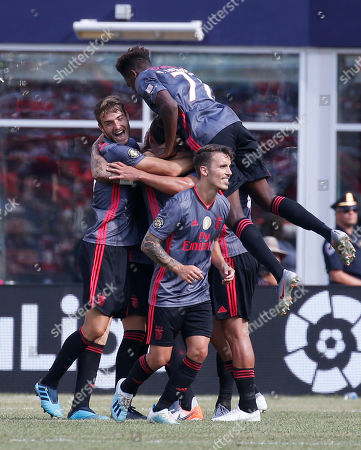 Benfica's Adel Taarabt, obscured, its congratulated by teammates after scoring a goal against AC Milan during the second half of an International Champions Cup soccer match, in Foxborough, Mass