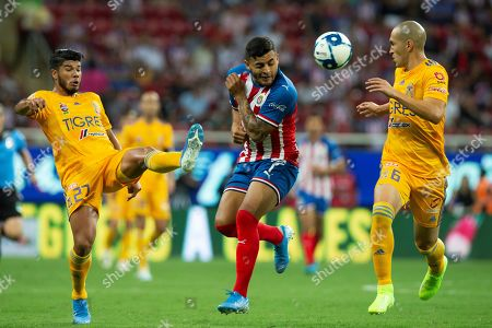 Stock Picture of Alexis Vega (C) of Chivas in action against Jair Diaz (L) and Jorge Torres (R) of Tigres UANL during the Apertura Tournament soccer match held at Akron Stadium, in Guadalajara, Mexico, 28 July 2019.