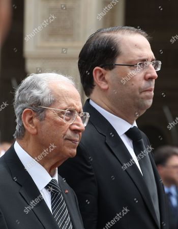 Stock Photo of The interim Tunisian President Mohamed Ennaceur (R) and Tunisian Prime Minister Youssef Chahed attend during the state funeral of late Tunisian president Beji Caid Essebsi at the Presidential Carthage Palace in Tunis