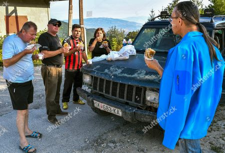 Stock Photo of Members of the Cakarovi family, husband Goce (2-L) and wife Vale (2-R), together with their friends eat breakfast on the road from Skopje?s district Dracevo towards the mountaineer?s home Karadzica (altitude of 1450m) on the mountain Jakupica, 45km south of Skopje, Republic of North Macedonia, 25 July 2019. Goce Cakarov manages the mountaineer home Karadzice and also keeps more than 50 beehives. Because of the high altitude, distance from any industrial or residential area (more than 40km) the honey that the bees produce belong to the category of high quality organic honey, even though it doesn?t have the certificate for organic products. According to him, a Macedonian family that has 100 beehives can produce around 1500kg of honey yearly. The high quality mountain-meadow honey is being sold for a minimal price of 8.5 euro per 0.7 litter jar, which means that the annual earnings are higher than 12,000 euro, or 20 percent higher than the average annual income of a Macedonian household. Beekeeping in North Macedonia is a rising business and is becoming an important part of modern lifestyle. A large number of young people are deciding to get into beekeeping, as stated by the president of the North Macedonian 'Beekeeping Federation' Jane Markov. According to the Ministry of Agriculture, in North Macedonia there are more than 7,000 families that work with beekeeping. The estimate of the Ministry is that in the country there were more than 240,000 beehives at the end of 2018. Depending on the weather conditions, one beehive produces from 18 up to 35 kg of honey. According to their data in 1992, North Macedonia produced more than 1,600 tons of honey. Due to the climate changes, weather conditions and the high increase in the use of pesticides, the honey production has sharply decreased. The estimate is that in 2018 the honey productin was around 400 tons.