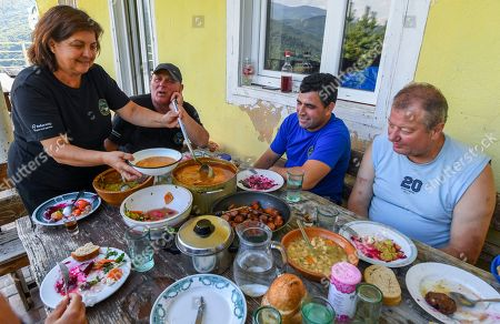 Members of the Cakarovi family, husband Goce (2-L) and wife Vale (L), together with their friends eat theit lunch after this year's first honey extraction from beehives situated next to the mountaineer?s home Karadzica (altitude of 1450m) on the mountain Jakupica, 45km south of Skopje, Republic of North Macedonia, 25 July 2019. Goce Cakarov manages the mountaineer home Karadzice and also keeps more than 50 beehives. Because of the high altitude, distance from any industrial or residential area (more than 40km) the honey that the bees produce belong to the category of high quality organic honey, even though it doesn?t have the certificate for organic products. According to him, a Macedonian family that has 100 beehives can produce around 1500kg of honey yearly. The high quality mountain-meadow honey is being sold for a minimal price of 8.5 euro per 0.7 litter jar, which means that the annual earnings are higher than 12,000 euro, or 20 percent higher than the average annual income of a Macedonian household. Beekeeping in North Macedonia is a rising business and is becoming an important part of modern lifestyle. A large number of young people are deciding to get into beekeeping, as stated by the president of the North Macedonian 'Beekeeping Federation' Jane Markov. According to the Ministry of Agriculture, in North Macedonia there are more than 7,000 families that work with beekeeping. The estimate of the Ministry is that in the country there were more than 240,000 beehives at the end of 2018. Depending on the weather conditions, one beehive produces from 18 up to 35 kg of honey. According to their data in 1992, North Macedonia produced more than 1,600 tons of honey. Due to the climate changes, weather conditions and the high increase in the use of pesticides, the honey production has sharply decreased. The estimate is that in 2018 the honey productin was around 400 tons.