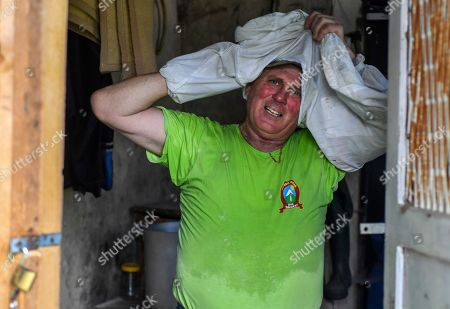 Beekeeper Goce Cakarov takes off his safety suit after this year's first honey extraction from beehives situated next to the mountaineer?s home Karadzica (altitude of 1450m) on the mountain Jakupica, 45km south of Skopje, Republic of North Macedonia, 25 July 2019. Goce Cakarov manages the mountaineer home Karadzice and also keeps more than 50 beehives. Because of the high altitude, distance from any industrial or residential area (more than 40km) the honey that the bees produce belong to the category of high quality organic honey, even though it doesn?t have the certificate for organic products. According to him, a Macedonian family that has 100 beehives can produce around 1500kg of honey yearly. The high quality mountain-meadow honey is being sold for a minimal price of 8.5 euro per 0.7 litter jar, which means that the annual earnings are higher than 12,000 euro, or 20 percent higher than the average annual income of a Macedonian household. Beekeeping in North Macedonia is a rising business and is becoming an important part of modern lifestyle. A large number of young people are deciding to get into beekeeping, as stated by the president of the North Macedonian 'Beekeeping Federation' Jane Markov. According to the Ministry of Agriculture, in North Macedonia there are more than 7,000 families that work with beekeeping. The estimate of the Ministry is that in the country there were more than 240,000 beehives at the end of 2018. Depending on the weather conditions, one beehive produces from 18 up to 35 kg of honey. According to their data in 1992, North Macedonia produced more than 1,600 tons of honey. Due to the climate changes, weather conditions and the high increase in the use of pesticides, the honey production has sharply decreased. The estimate is that in 2018 the honey productin was around 400 tons.