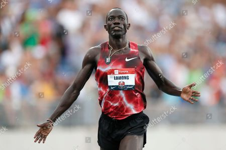 Lopez Lomong crosses the finish line as he wins the men's 5,000-meter run at the U.S. Championships athletics meet, in Des Moines, Iowa