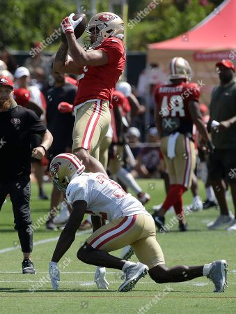 San Francisco 49ers' Shawn Poindexter, top, catches a pass over D.J. Reed Jr. at the team's NFL football training camp in Santa Clara, Calif