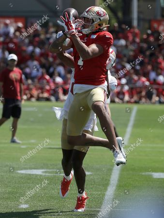 San Francisco 49ers' Shawn Poindexter, top, tries to catch a pass at the team's NFL football training camp in Santa Clara, Calif