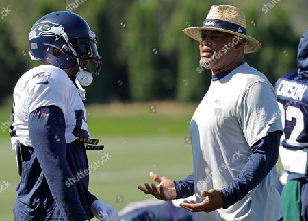 Seattle Seahawks middle linebacker Bobby Wagner, left, talks with defensive coordinator Ken Norton Jr., right, during NFL football training camp in Renton, Wash