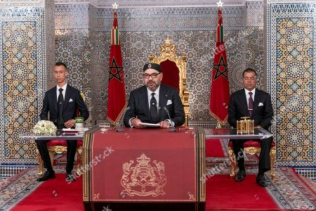 """In this photo provided by the Moroccan News Agency (MAP), Morocco's King Mohammed VI, center, accompanied by his son Crown Prince Moulay Hassan, left, and brother Prince Moulay Rashid addresses the Nation in a speech aired on TV, at the Royal Palace in Tetouan, Morocco, on . Morocco's king is calling for a government reshuffle, seeking """"new blood"""" and saying the country's current development policy isn't doing enough to meet Moroccans' needs. In a speech Monday night marking his 20 years on the throne, King Mohammed VI reproached the Islamist-led government and tasked Prime Minister Saad-Eddine El Othmani with proposing new government candidates in the fall"""
