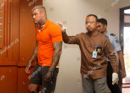 British national Terence Murrell, left, is escorted by immigration officers during a press conference in Bali, Indonesia, . Indonesian authorities say they arrested the alleged British fugitive in Bali in possession of pornography and drugs
