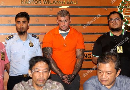 Immigration officers flank British national Terence Murrell, center, as he is presented to the media during a press conference in Bali, Indonesia, . Indonesian authorities say they arrested the alleged British fugitive in Bali in possession of pornography and drugs