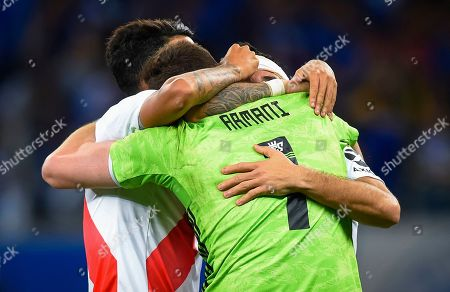 Players hug Franco Armani, goalkeeper of Argentina's River Plate, as they celebrate their victory over Brazil's Cruzeiro during a Copa Libertadores soccer match in Belo Horizonte, Brazil