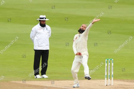 Umpire Aleem Dar looks on as Moeen Ali of England bowls the ball