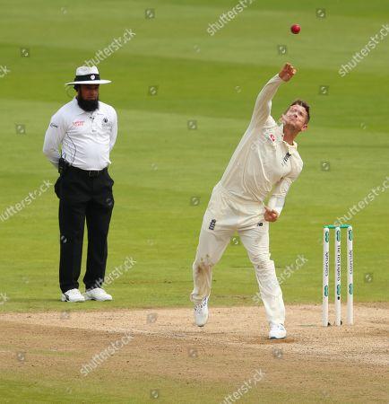 Umpire Aleem Dar looks on as Joe Denly of England bowls the ball