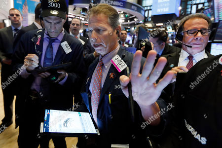 Trader Robert Charmak, center, works on the floor of the New York Stock Exchange, . Stocks are opening slightly higher on Wall Street led by gains in Apple and other technology companies