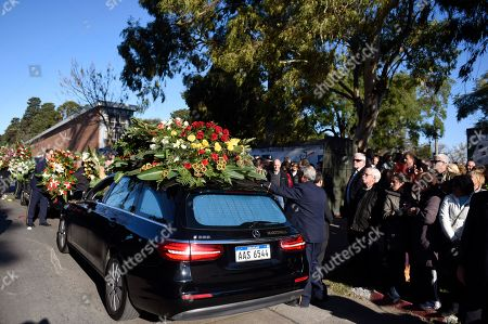 People pay their respects as the hearse carrying the body of María Auxiliadora Delgado, wife of Uruguay's President Tabare Vazquez, drives by, in Montevideo, Uruguay, . Uruguay's presidency confirmed that Delgado died of a heart attack during the early morning hours