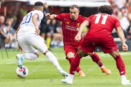 Liverpool's Xherdan Shaqiri (C) in action against Lyon's Fernando Marcal (L) during a friendly soccer match between Liverpool FC and Olympique Lyon in Geneva, Switzerland, 31 July 2019.