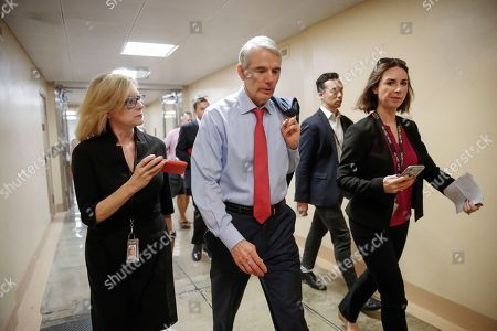 Sen. Rob Portman, R-Ohio, is flanked by reporters as he walks to the Senate chamber for votes on federal judges as a massive budget pact between House Speaker Nancy Pelosi and President Donald Trump is facing a key vote in the GOP-held Senate later, at the Capitol in Washington, . Many conservatives in the Republican-led Senate are torn between supporting President Donald Trump and risking their political brand with an unpopular vote to add $2 trillion or more to the federal debt