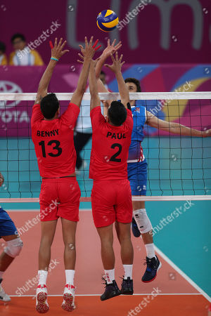 Pelegrin Vargas, Benny Bernaola. Pelegrin Vargas, of Puerto Rico, right, attacks Benny Bernaola, left, and Paul Williams of Peru, during their men's volleyball preliminary round match at the Pan American Games in Lima Peru