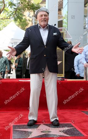 Stacy Keach poses atop his star following a ceremony honoring him with a star at the Hollywood Walk of Fame, in Los Angeles