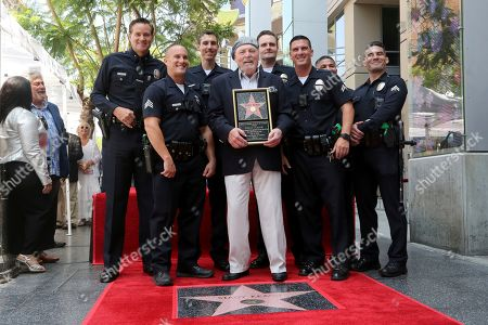 Stacy Keach, center, pose with officers of the LAPD Hollywood Division as he holds a miniuaturette of a star after a ceremony honoring Stacy Keach with a star at the Hollywood Walk of Fame, in Los Angeles
