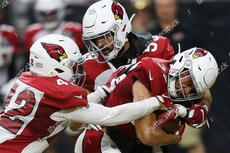 Arizona Cardinals running back D.J. Foster, right, gets tackled by defensive back Jonathan Owens (42) and linebacker Joe Walker, top, during NFL football training camp, in Glendale, Ariz