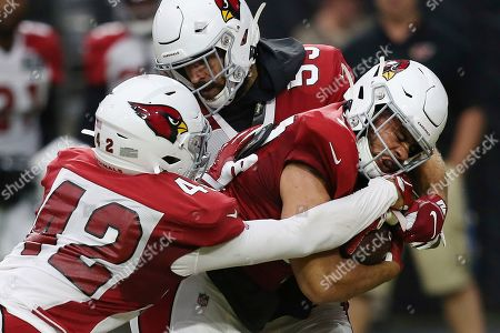 Arizona Cardinals running back D.J. Foster, right, gets tackled by Cardinals defensive back Jonathan Owens (42) and Cardinals linebacker Joe Walker, top, during an NFL football training camp practice, in Glendale, Ariz
