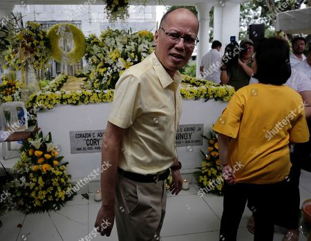 Stock Photo of Former Filipino President Benigno 'Noynoy' Aquino III (C) stands next to the tomb of former President Corazon 'Cory' Aquino and former Senator Benigno 'Ninoy' Aquino during a mass in Paranaque City, Philippines, 01 August 2019. Family, relatives, and supporters of former president  Corazon Aquino, the first woman president who led the period of transition back to democratic government in 1986 after 20 years of martial law and authoritarian rule, offered a tribute on her 10th death anniversary on her grave on 01 August.