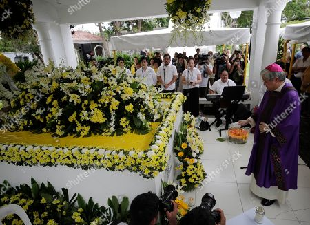 Stock Image of A Filipino priest blesses the tomb of former President Corazon 'Cory' Aquino and former Senator Benigno 'Ninoy' Aquino during a mass in Paranaque City, Philippines, 01 August 2019. Family, relatives, and supporters of former president  Corazon Aquino, the first woman president who led the period of transition back to democratic government in 1986 after 20 years of martial law and authoritarian rule, offered a tribute on her 10th death anniversary on her grave on 01 August.