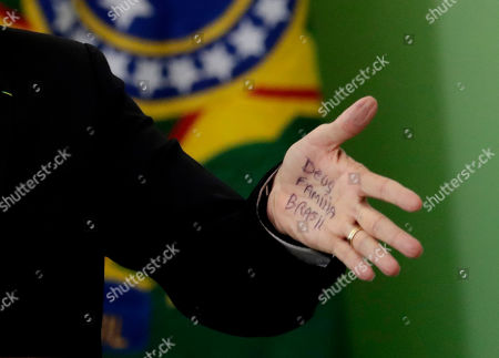 """Brazil's President Jair Bolsonaro's hand shows notes for his speech that read in Portuguese """"God, Family, Brazil,"""" during the launching ceremony of the Doctors for Brazil Program, at the Planalto Presidential Palace, in Brasilia, Brazil, . According to the government, the Doctors for Brazil Program will replace the program implemented by Former President Dilma Rousseff with the help of Cuban doctors, replacing them with Brazilian doctors"""