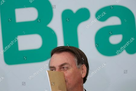 Stock Image of Brazil's President Jair Bolsonaro covers his face as he speaks to an aide during the launching ceremony of the Doctors for Brazil Program, at the Planalto Presidential Palace, in Brasilia, Brazil, . According to the government, the Doctors for Brazil Program will replace the program implemented by Former President Dilma Rousseff with the help of Cuban doctors, replacing them with Brazilian doctors