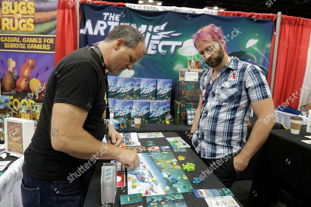 Daniel Rocchi, left, shows David Phillips how to play a game during the Gen Con convention at the Indiana Convention Center, in Indianapolis. The annual convention for consumer fantasy, electronic, sci-fi, adventure and hobby gaming runs until Sunday