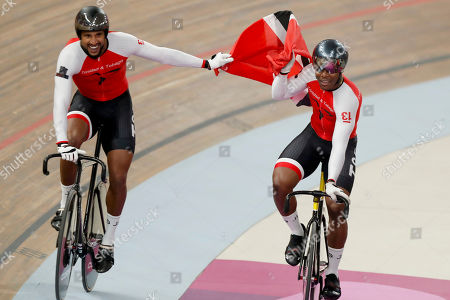 Trinidad and Tobago cycling team members, composed of Keron Bramble, Paul Nicholas and Njisane Phillip, celebrate winning the gold medal in the cycling track men's team sprint at the Pan American Games in Lima, Peru