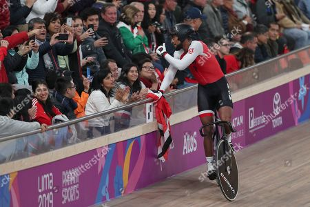 Njisane Phillip greets spectators after winning with teammates Keron Bramble and Paul Nicholas the gold medal in the cycling track men's team sprint final at the Pan American Games in Lima, Peru