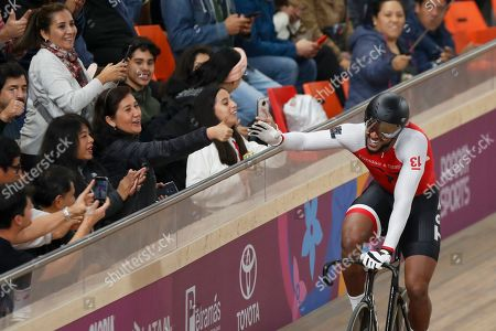 Njisane Phillip greets spectators after winning, with teammates Keron Bramble and Paul Nicholas, the gold medal in the cycling track men's team sprint final at the Pan American Games in Lima, Peru