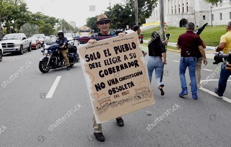 A protester holds a sign that reads 'Only the people must choose its Governor, not an obsolete constitution' during an ordinary session at Congress to confirm the appointment of Pedro Pierluisi as Secretary of Sate, in San Juan, Puerto Rico, 01 August 2019. If appointed as Secretary of State, Pierluisi will replace Governor Ricardo Rossello according to Puerto Rico's law, who will officially resign on the following day after a national crisis triggered by the leak of controversial private chats, if he gets the required number of votes. The Justice Secretary Wanda Vazquez will be next in line if the position of Secretary of State was not filled by 02 August.