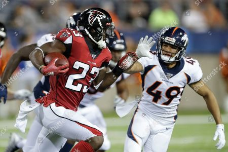 Atlanta Falcons running back Brian Hill (23) runs the ball against Denver Broncos cornerback Alijah Holder (49) during the second half of the Pro Football Hall of Fame NFL preseason game, in Canton, Ohio