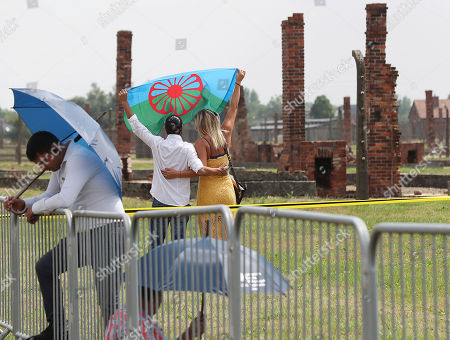 Stock Photo of People display a Romani flag to commemorate the Roma and Sinti people killed by Nazi Germany in World War II, during ceremonies, in Oswiecim, Poland, . The American civil rights activist Rev. Jesse Jackson gathered Friday with survivors at the former Nazi death camp of Auschwitz-Birkenau to commemorate an often forgotten genocide ? that of the Roma people