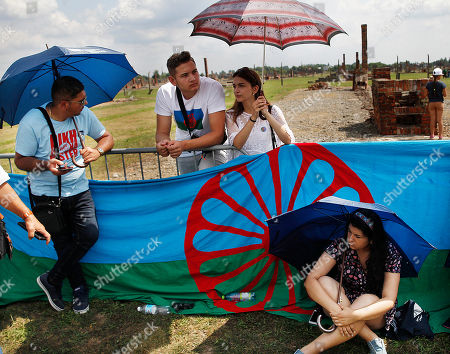 People display a Romani flag to commemorate the Roma and Sinti people killed by Nazi Germany in World War II, during ceremonies, in Oswiecim, Poland, . The American civil rights activist Rev. Jesse Jackson gathered Friday with survivors at the former Nazi death camp of Auschwitz-Birkenau to commemorate an often forgotten genocide ? that of the Roma people