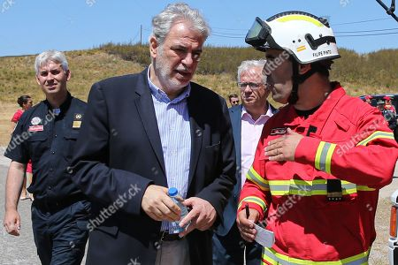 Stock Photo of European Commissioner for Humanitarian Aid and Crisis Management Christos Stylianides (2-L) with Portuguese Minister of Internal Administration Eduardo Cabrita (2-R), talks to a firefighter during a visit to Portimo, Portugal, 02 August 2019.