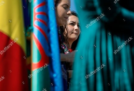 """Stock Picture of A girl gestures, behind the Romanian and Roma flags, during a commemoration of the Roma Holocaust Memorial Day, in Bucharest, Romania, . During the event Romania's minister of culture Daniel Breaz described the WWII plight of the Romanian Roma, when, according to the Elie Wiesel Institute for the Study of the Holocaust in Romania 50,000 Roma were deported to Trans-Dniester in the Soviet Union and 11,000 died as """"delicate moments, when unpleasant things happened and certain minorities suffered"""