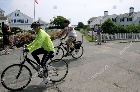 Bicyclists pedal past the street leading to the Kennedy compound, in Hyannis Port, Mass. Saoirse Kennedy Hill, granddaughter of Ethel Kennedy and her late husband Robert F. Kennedy, died at the compound on Thursday. She was 22