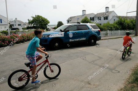 A police car patrols past the street leading to the Kennedy compound, in Hyannis Port, Mass. Saoirse Kennedy Hill, granddaughter of Ethel Kennedy and her late husband Robert F. Kennedy, died at the compound Thursday. She was 22